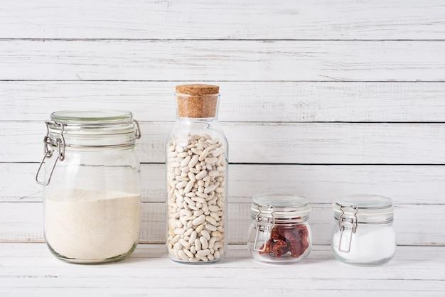 Os utensílios da cozinha surgem com os recipientes de vidro reutilizáveis com ingredientes alimentares. zero conceito de resíduos Foto Premium