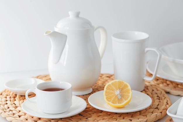 Os utensílios de mesa cerâmicos brancos, o placemat redondo trançado fibra e a cutelaria ajustaram-se no fundo branco. estilo escandinavo. Foto Premium