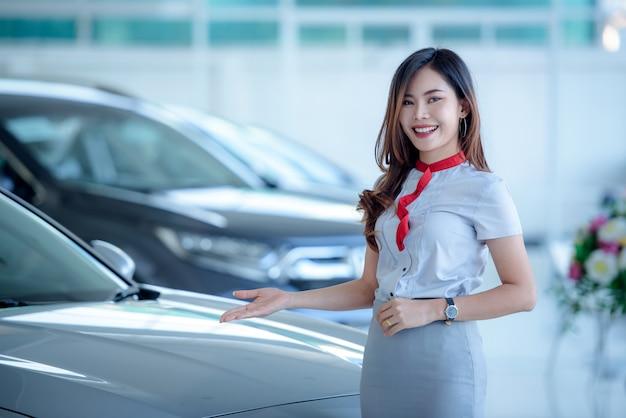 Os vendedores asiáticos bonitos têm o prazer de vender carros novos no showroom e os clientes vêm comprar carros nas concessionárias. Foto Premium