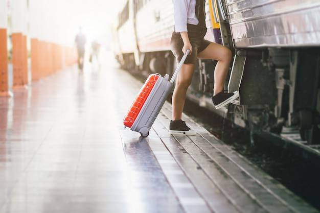 Os viajantes grávidos da mulher estão tomando um trem com levar sua bolsa vermelha do trole no curso da estação de trem. Foto Premium