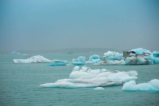 Os viajantes tomam um barco para ver o gelo flutuante nos icebergs do oceano na lagoa da geleira de jokulsarlon, islândia Foto Premium