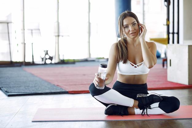 Ostenta a mulher treinando em uma academia de manhã Foto gratuita