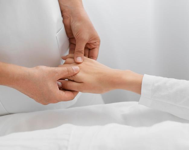 Osteopata tratando o braço de um paciente Foto gratuita