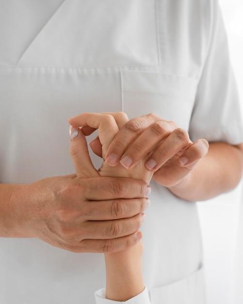 Osteopata tratando os braços de um paciente Foto gratuita
