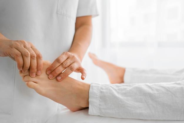Osteopata tratando um paciente em pé Foto gratuita