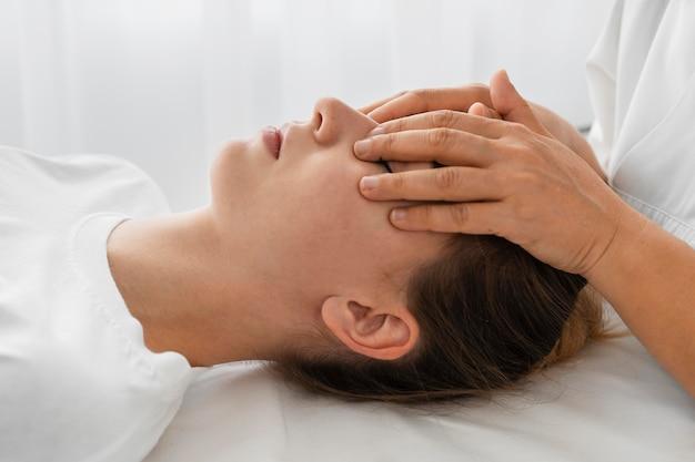 Osteopata tratando um paciente massageando seu rosto Foto gratuita