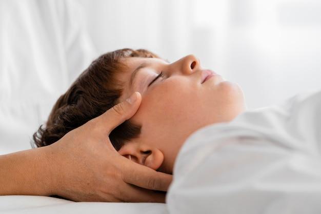 Osteopata tratando uma criança massageando sua cabeça Foto gratuita