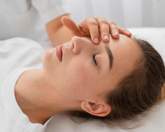 Osteopata tratando uma paciente massageando o rosto em close-up Foto gratuita