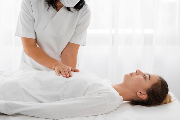 Osteopata tratando uma paciente massageando seu corpo Foto gratuita