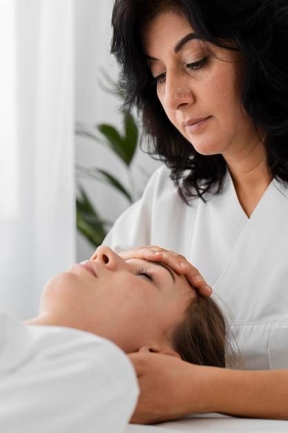 Osteopata tratando uma paciente massageando seu rosto Foto gratuita