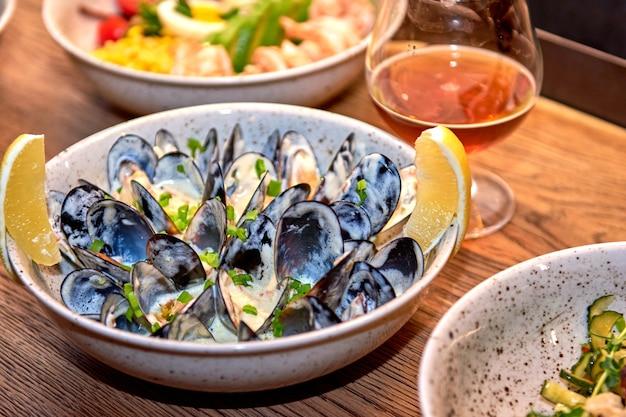 Ostras deliciosas no restaurante sobre uma mesa de madeira, sem pessoas visíveis. saborosos frutos do mar com cerveja no menu do café ou pub. Foto Premium