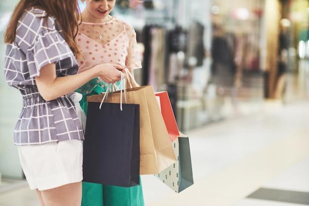 Ótimo dia para fazer compras. duas mulheres bonitas olham para a bolsa e se gabam do que compraram Foto gratuita