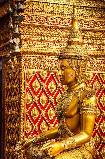 Ouro sentado estátua de buda na tailândia Foto Premium