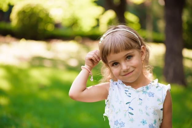 Outdoorin pequeno bonito da moça um parque. Foto Premium