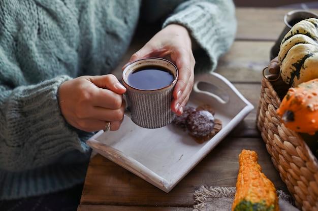 Outono, abóboras, xícara fumegante quente de café em uma mesa de madeira. sazonal, café da manhã com biscoitos de canela, domingo relaxante. garota com uma camisola com um copo em galinhas Foto Premium