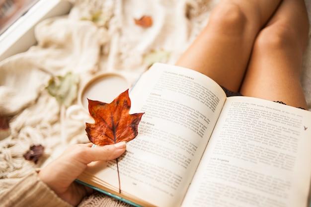 Outono ainda a vida. vista de cima. a menina lê um livro aberto enquanto está sentado em uma manta Foto Premium