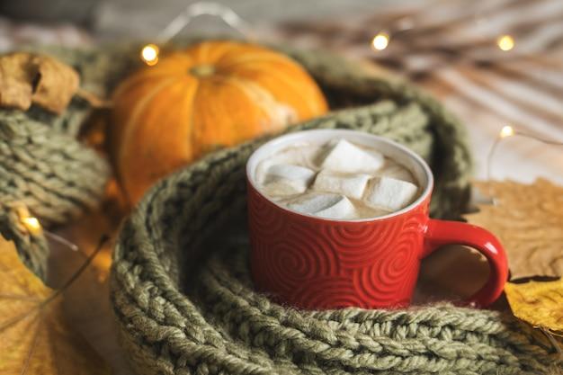 Outono ainda vida de abóbora, folhas, cachecol, caneca vermelha de cacau com marshmallow Foto Premium