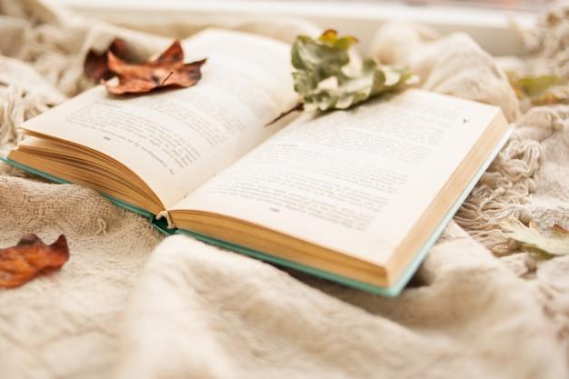 Outono ainda vida.um livro aberto está mentindo sobre um tapete bege, folhas caídas outonais estão mentindo sobre o livro. Foto Premium