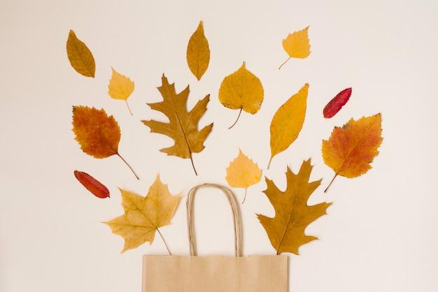 Outono compras com descontos. vendas de outono. crafting saco de compra de papel bege, de que olhar para fora as folhas amarelas do outono. Foto Premium
