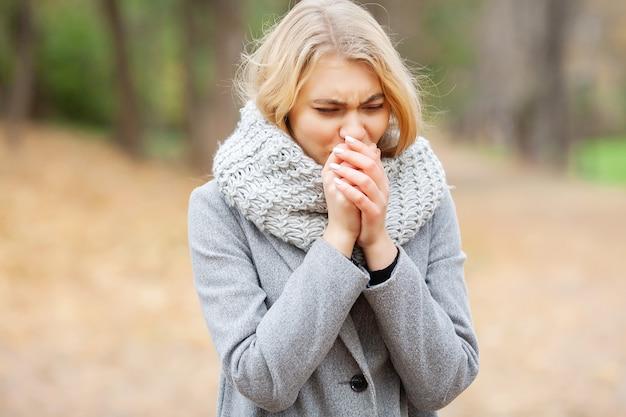 Outono frio. mulher vestindo máscara facial e segurando comprimidos entre árvores florescendo no parque Foto Premium