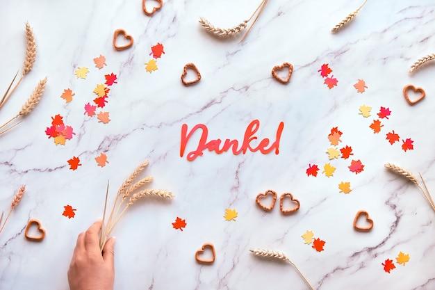 Outono fundo sazonal com espigas de trigo e confetes de papel. o texto em papel danke significa obrigado em alemão. Foto Premium