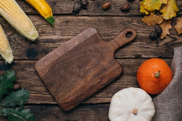 Outono legumes: abóboras e milho com folhas amarelas e cortar a tábua na madeira Foto Premium