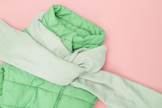 Outono plana leigos com cores de tendência de roupas quentes em fundo rosa. roupas de moda brilhante para a mulher. jaqueta para baixo neo hortelã colorida, cachecol largo de têxteis. vista do topo. postura plana. Foto Premium