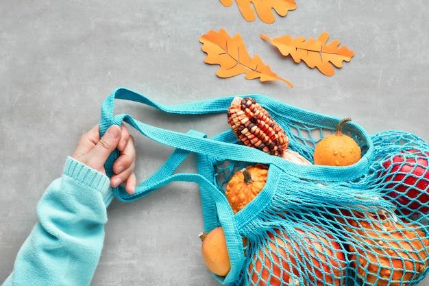 Outono plano leigos com saco de corda turquesa com abóboras laranja, top vie em pedra cinza Foto Premium