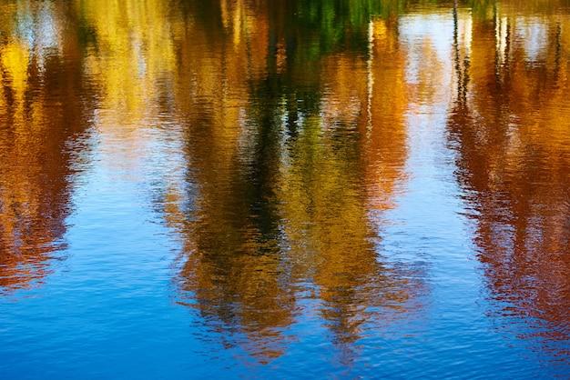 Outono. reflexo de árvores de outono coloridas borradas no rio Foto Premium