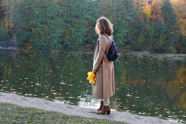 Outono. uma jovem mulher fica na margem do lago e olha para a distância. ela está vestida com roupas da moda em bege. nas mãos dela, ela tem um buquê de folhas de bordo. Foto Premium
