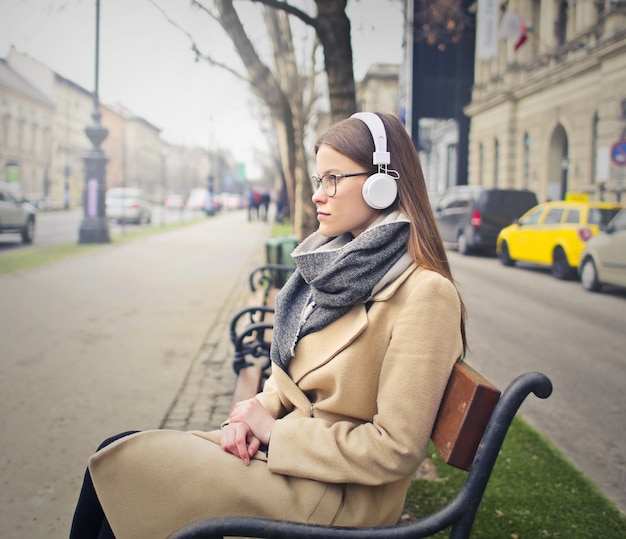Ouvindo música em um banco da cidade Foto Premium