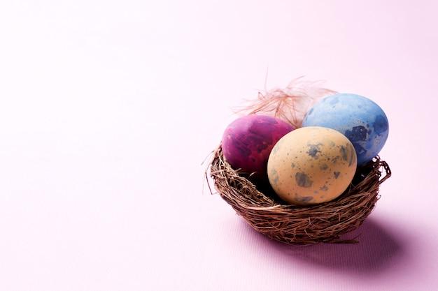 Ovo da páscoa colorido no ninho no fundo cor-de-rosa com espaço da cópia. Foto Premium