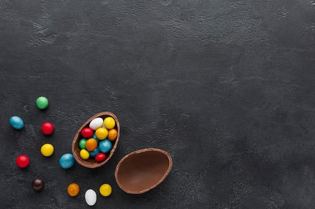 Ovo de páscoa de chocolate cheio de doces coloridos Foto gratuita