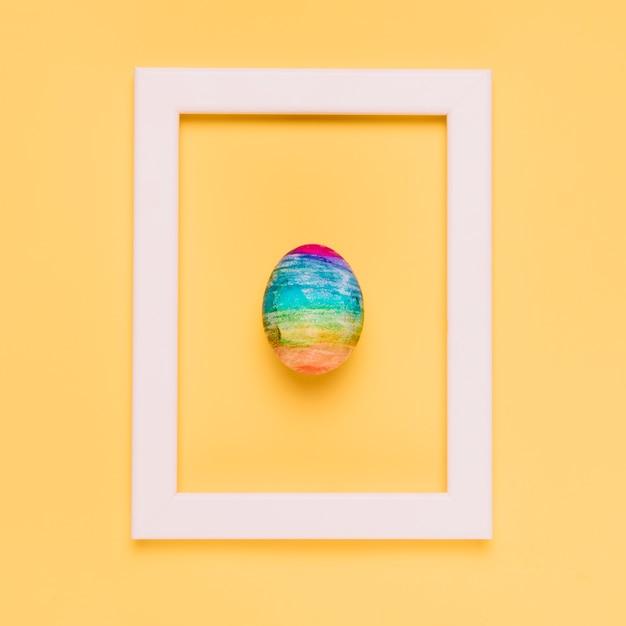 Ovo de páscoa multicolorido dentro da moldura de borda branca em pano de fundo amarelo Foto gratuita