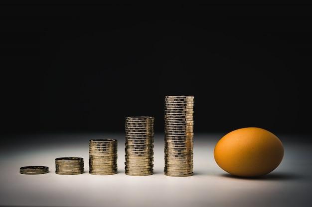 Ovo e muitos dinheiro com gráfico de inflação pilhas de moedas Foto Premium