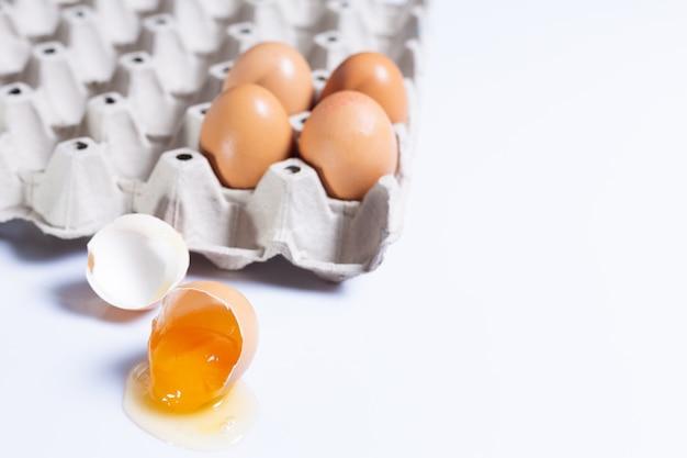 Ovo em uma bandeja com ovo quebrado para uso na culinária Foto Premium
