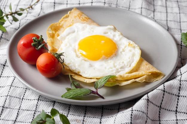Ovo frito com crepe e tomate cereja Foto Premium