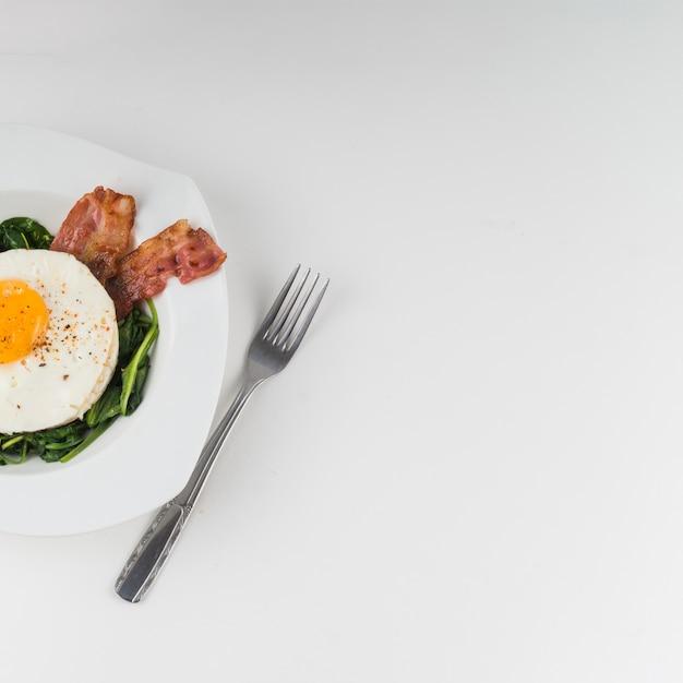 Ovo frito com espinafre e bacon na chapa contra fundo branco Foto gratuita