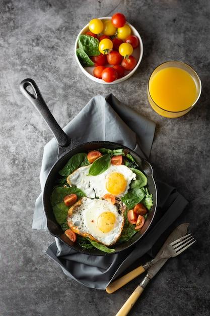 Ovo frito em uma panela, servido com tomates cereja frescos, café da manhã saudável, Foto Premium