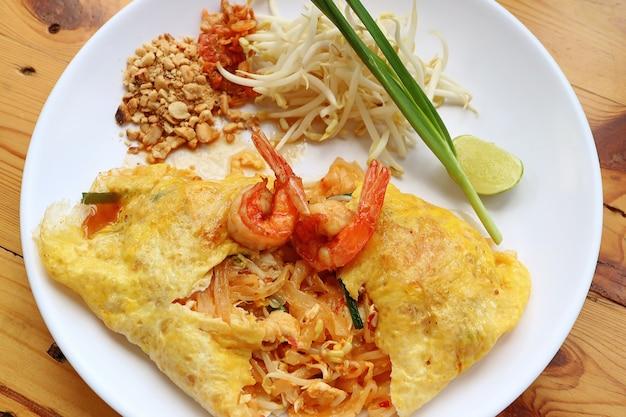 Ovo frito estilo tailandês envolto stir fried noodle ou pad thai coberto com camarões servido Foto Premium