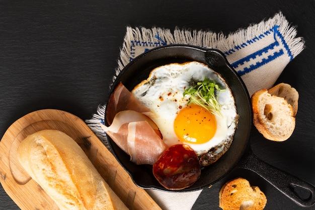 Ovo frito na panela de frigideira com brotos de linho e bacon com espaço de cópia Foto Premium