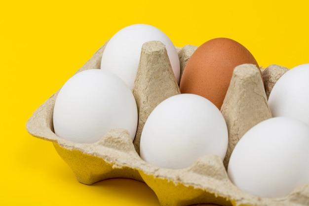 Ovo marrom entre ovos brancos em caixa em fundo amarelo Foto Premium