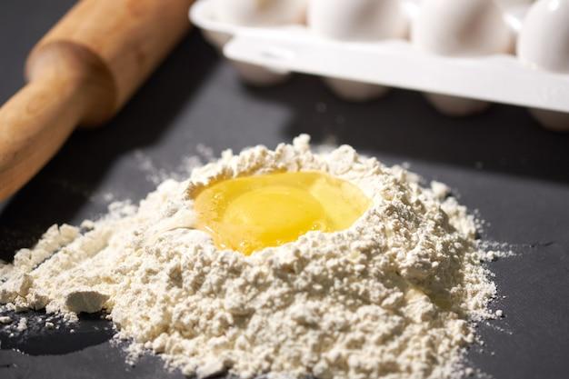 Ovo quebrado na farinha, ao lado de um rolo e ovos inteiros Foto Premium