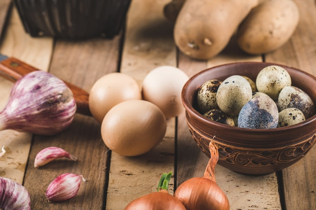Ovos, alho e cebola em uma placa de madeira Foto gratuita