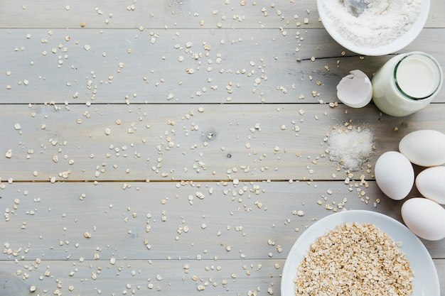Ovos; aveia; leite; farinha; e açúcar no fundo de madeira Foto gratuita