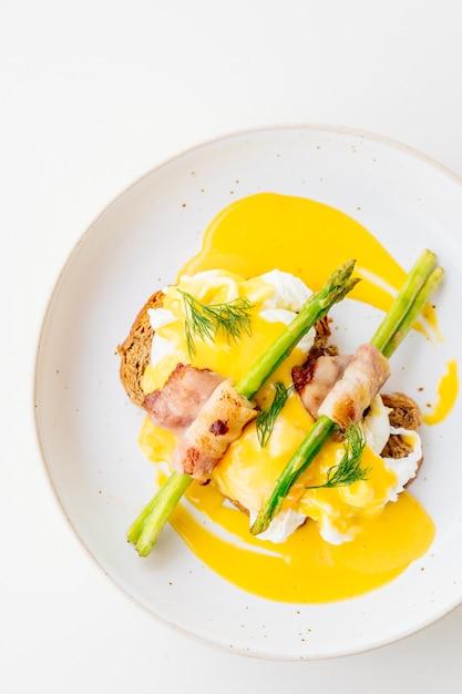 Ovos benedict com bacon torcer espargos Foto gratuita