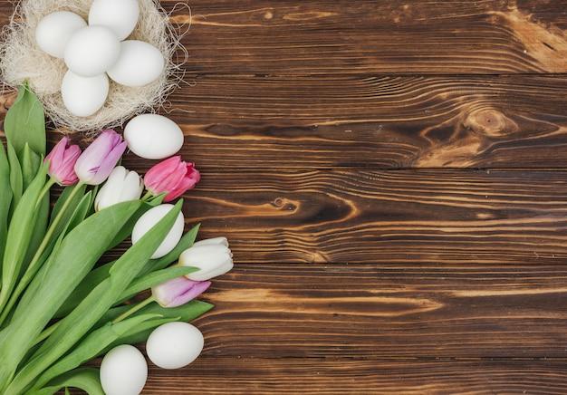 Ovos brancos no ninho com tulipas brilhantes na mesa de madeira Foto gratuita