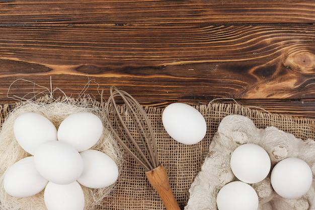 Ovos brancos no ninho e em rack com bata na mesa Foto gratuita