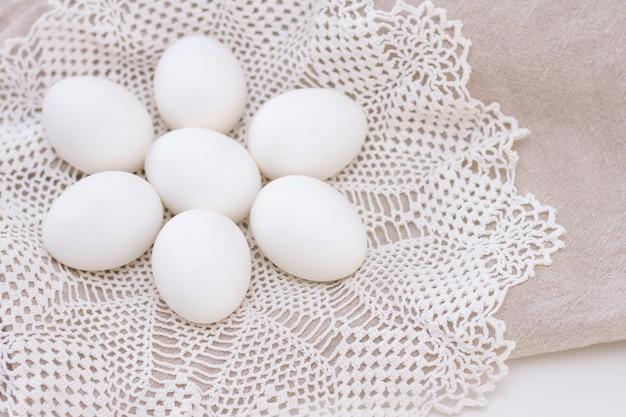 Ovos brancos orgânicos de frango frescura nutrição saudável em um saco marrom e um guardanapo de malha branco lindo em forma de uma flor. Foto Premium