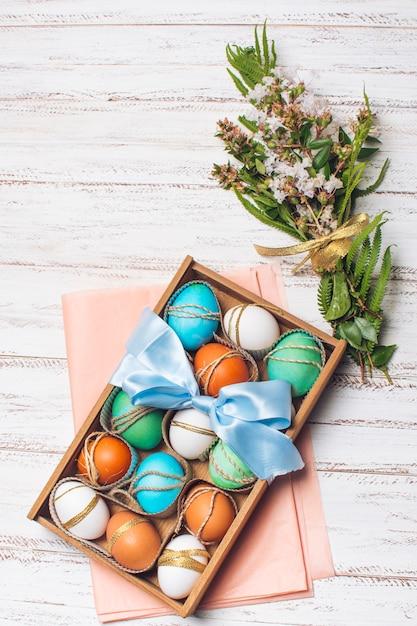 Ovos brilhantes em caixa em papel ofício rosa perto monte de plantas Foto gratuita